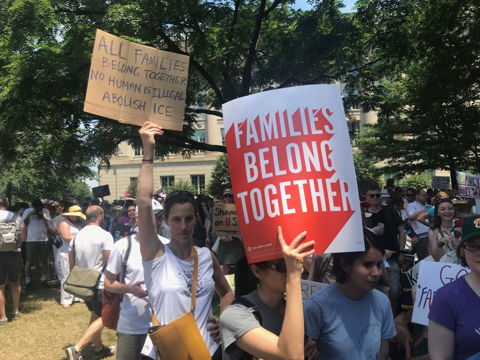 "Under a scorching sun, a big crowd of demonstrators jammed Lafayette Park and spilled over into Farragut Square to protest the Trump administration's immigration policies for the ""Families Belong Together"" march and rally Saturday in downtown D.C. (WTOP/Dick Uliano)"