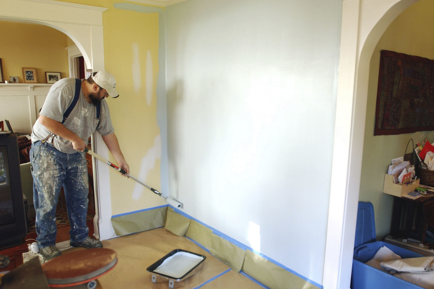 FILE- In this Dec. 5, 2008, file photo, painting contractor Andrew Lohr finishes the first coat on his living room wall in Portland, Ore. Home improvements can rejuvenate a stale dwelling. A fresh coat of paint on the walls can make for a quick makeover. (AP Photo/Greg Wahl-Stephens, File)