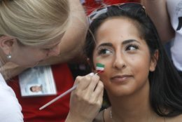 An artist draws an Iranian flag on the face of an Iranian fan prior the group B match between Morocco and Iran at the 2018 soccer World Cup in St.Petersburg, Russia, Friday, June 15, 2018. (AP Photo/Dmitri Lovetsky)