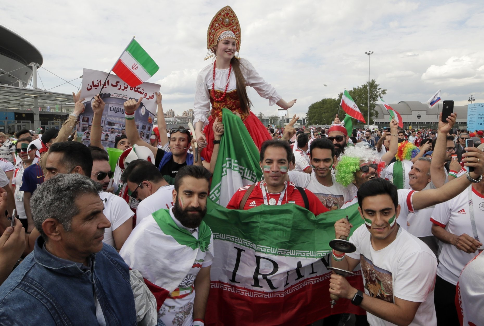 Iranian fans pose with a woman dressed a Russian national costume in front of 'Saint Petersburg' stadium prior the group B match between Morocco and Iran at the 2018 soccer World Cup in St.Petersburg, Russia, Friday, June 15, 2018. (AP Photo/Dmitri Lovetsky)