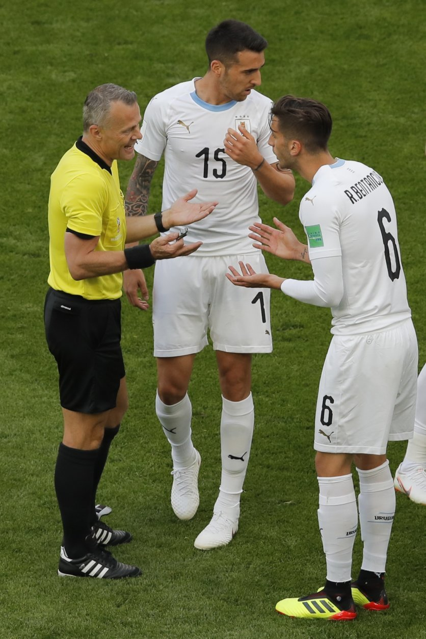 Uruguay's Rodrigo Bentancur, right, and Uruguay's Matias Vecino, center, talk to referee Bjorn Kuipers, left, during the group A match between Egypt and Uruguay at the 2018 soccer World Cup in the Yekaterinburg Arena in Yekaterinburg, Russia, Friday, June 15, 2018. (AP Photo/Vadim Ghirda)