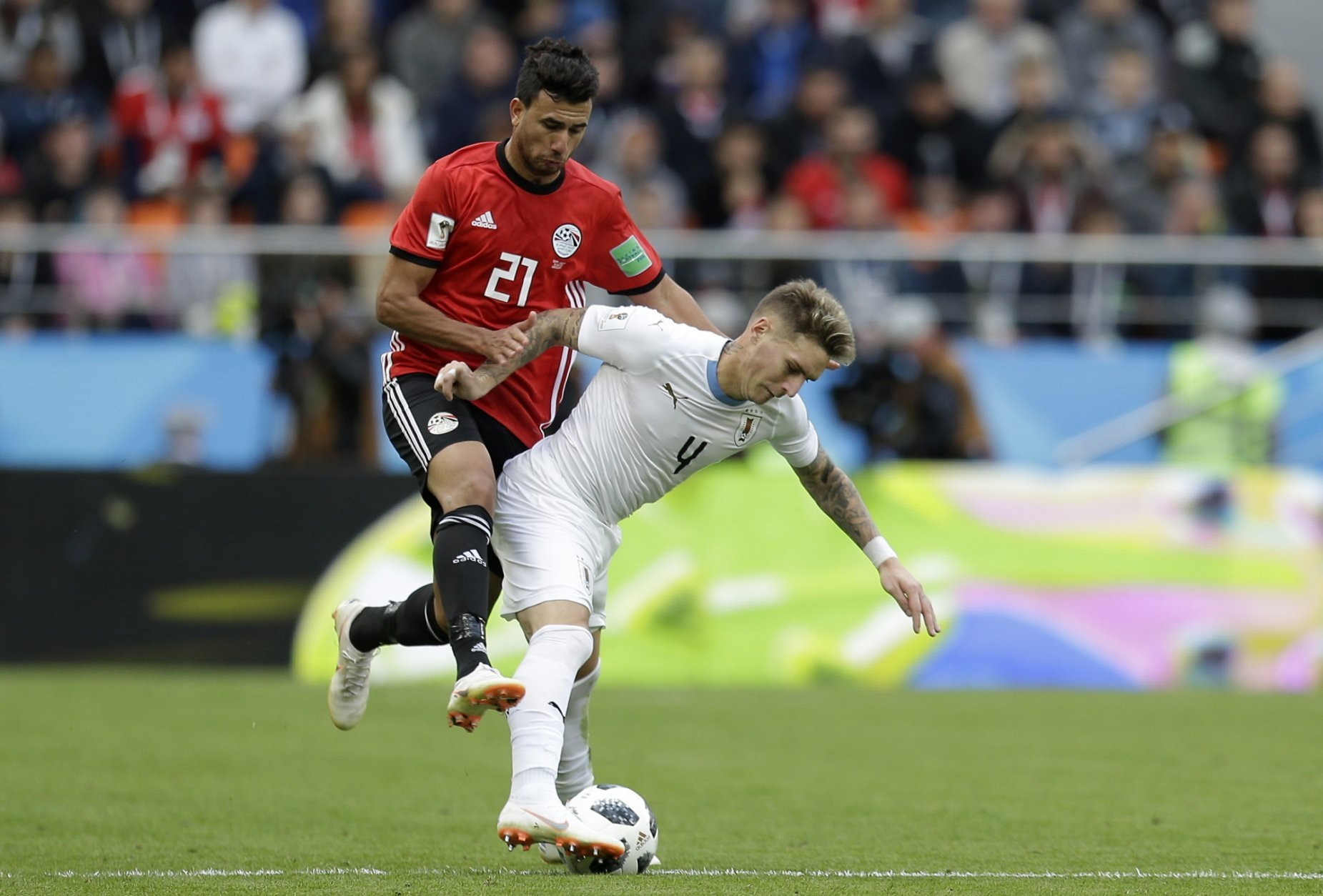 Uruguay's Guillermo Varela, right, challenges for the ball with Egypt's Trezeguet during the group A match between Egypt and Uruguay at the 2018 soccer World Cup in the Yekaterinburg Arena in Yekaterinburg, Russia, Friday, June 15, 2018. (AP Photo/Natacha Pisarenko)