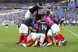 France's Paul Pogba, top, celebrates wit team mates after France's Kylian Mbappe scored his side's third goal during the round of 16 match between France and Argentina, at the 2018 soccer World Cup at the Kazan Arena in Kazan, Russia, Saturday, June 30, 2018. (AP Photo/David Vincent)