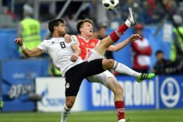 Egypt's Tarek Hamed, left, and Russia's Alexander Golovin compete for the ball during the group A match between Russia and Egypt at the 2018 soccer World Cup in the St. Petersburg stadium in St. Petersburg, Russia, Tuesday, June 19, 2018. (AP Photo/Martin Meissner)