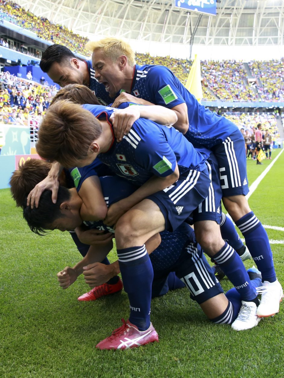 Teammates crowd over Japan's Shinji Kagawa after he scored from the penalty spot his side's first goal against Colombia during a group H match at the 2018 soccer World Cup in the Mordavia Arena in Saransk, Russia, Tuesday, June 19, 2018. (AP Photo/Eugene Hoshiko)