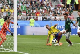 Mexico's Edson Alvarez, right, scores an own goal to give Sweden a 3-0 lead during the group F match between Mexico and Sweden, at the 2018 soccer World Cup in the Yekaterinburg Arena in Yekaterinburg , Russia, Wednesday, June 27, 2018. (AP Photo/Martin Meissner)