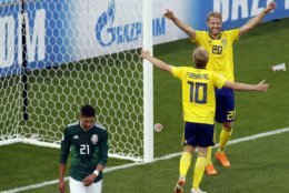 Sweden's Ola Toivonen, right, and Emil Forsberg celebrate after Mexico's Edson Alvarez, left, scores an own goal during the group F match between Mexico and Sweden, at the 2018 soccer World Cup in the Yekaterinburg Arena in Yekaterinburg , Russia, Wednesday, June 27, 2018. (AP Photo/Efrem Lukatsky)