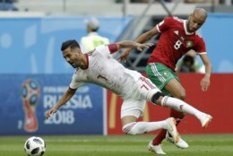 Iran's Masoud Shojaei, left, is tackled by Morocco's Karim El Ahmadi during the group B match between Morocco and Iran at the 2018 soccer World Cup in the St. Petersburg Stadium in St. Petersburg, Russia, Friday, June 15, 2018. (AP Photo/Andrew Medichini)