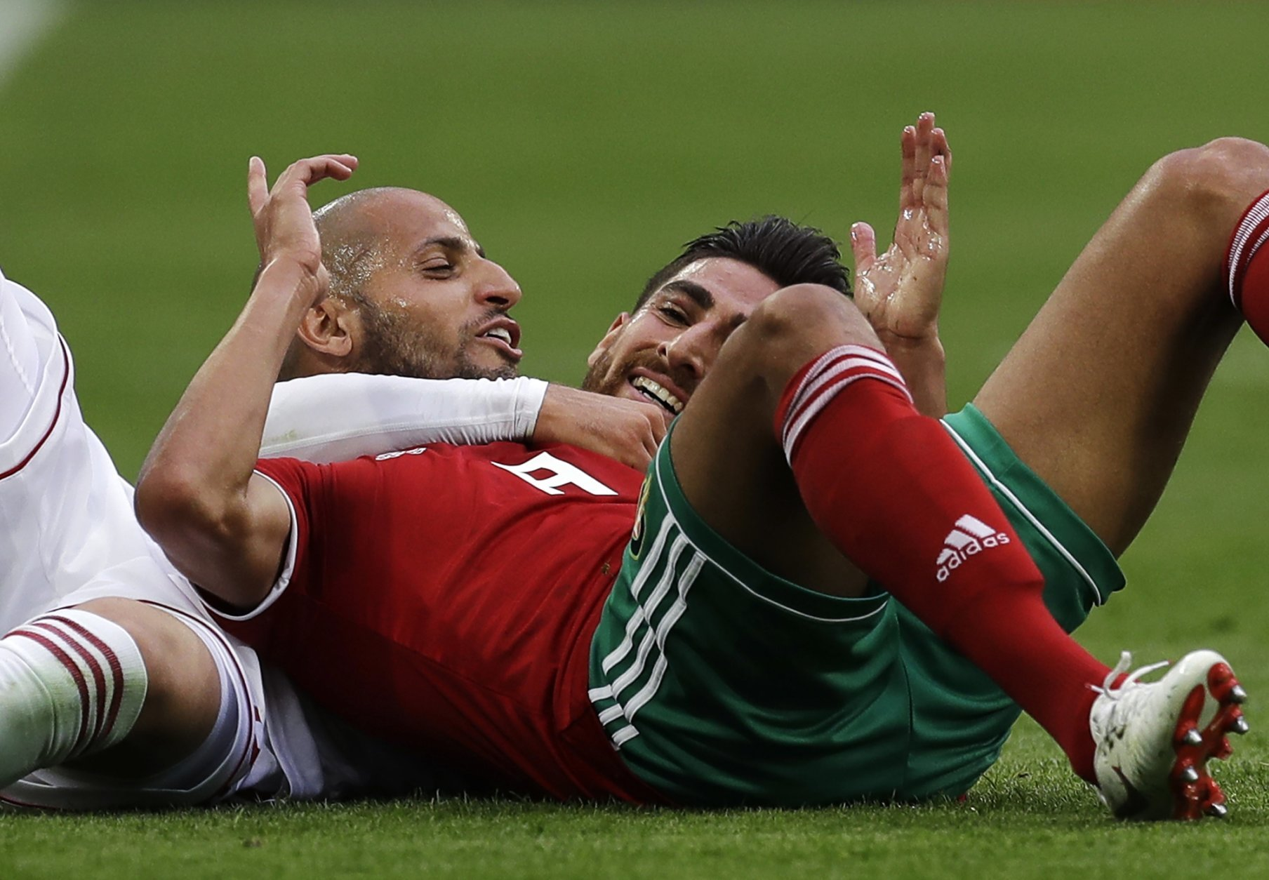 Morocco's Ayoub El Kaabi, front, and Iran's Alireza Jahanbakhsh, rear, smile after they collide to compete the ball during the group B match between Morocco and Iran at the 2018 soccer World Cup in the St. Petersburg Stadium in St. Petersburg, Russia, Friday, June 15, 2018. (AP Photo/Themba Hadebe)