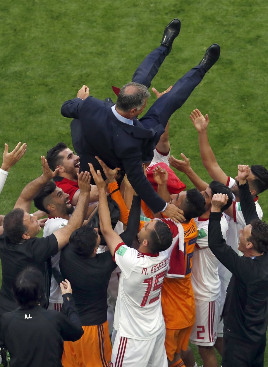 Players of Iran celebrate with their coach Carlos Queiroz after the group B match between Morocco and Iran at the 2018 soccer World Cup in the St. Petersburg Stadium in St. Petersburg, Russia, Friday, June 15, 2018. (AP Photo/Darko Vojinovic)
