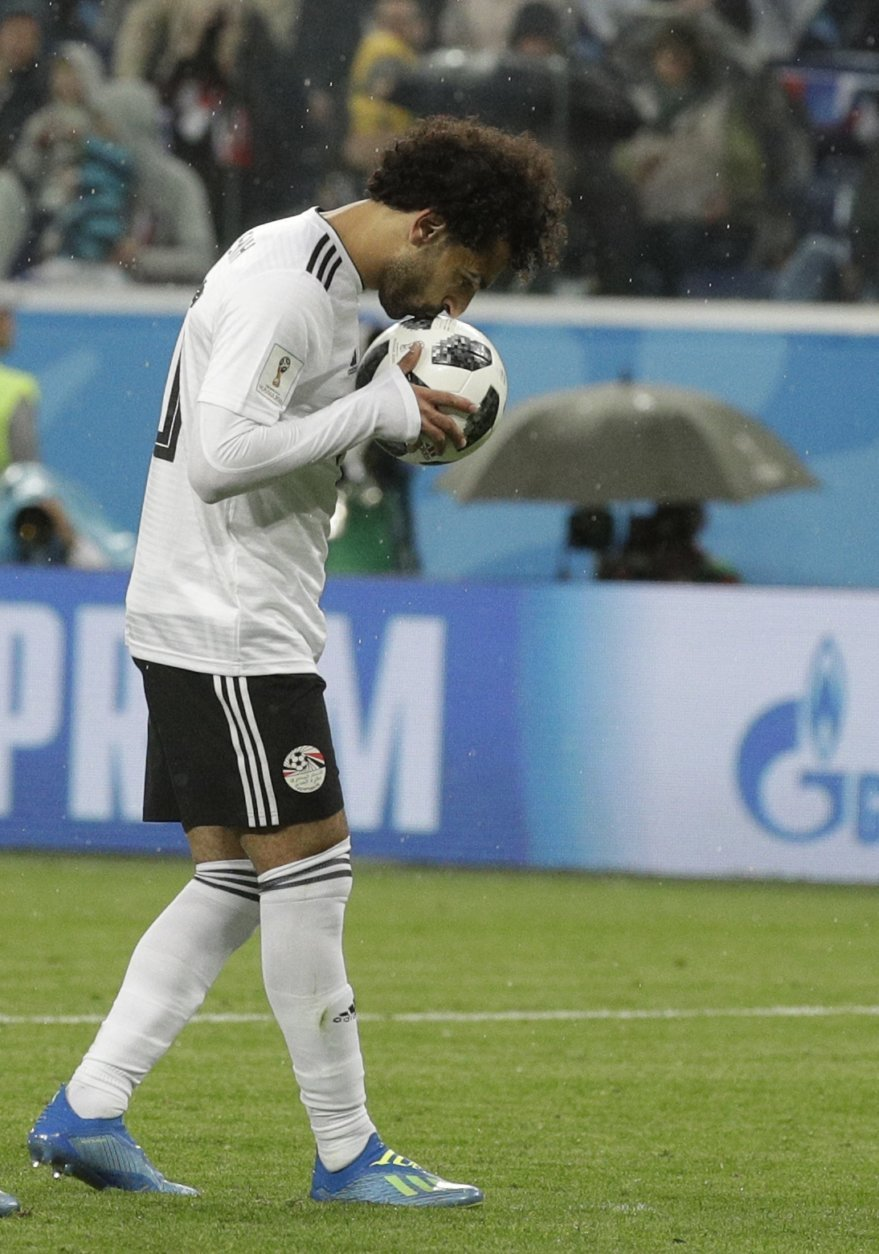 Egypt's Mohamed Salah kisses the ball before scoring his sides first goal from a penalty kick during the group A match between Russia and Egypt at the 2018 soccer World Cup in the St. Petersburg stadium in St. Petersburg, Russia, Tuesday, June 19, 2018. (AP Photo/Gregorio Borgia)