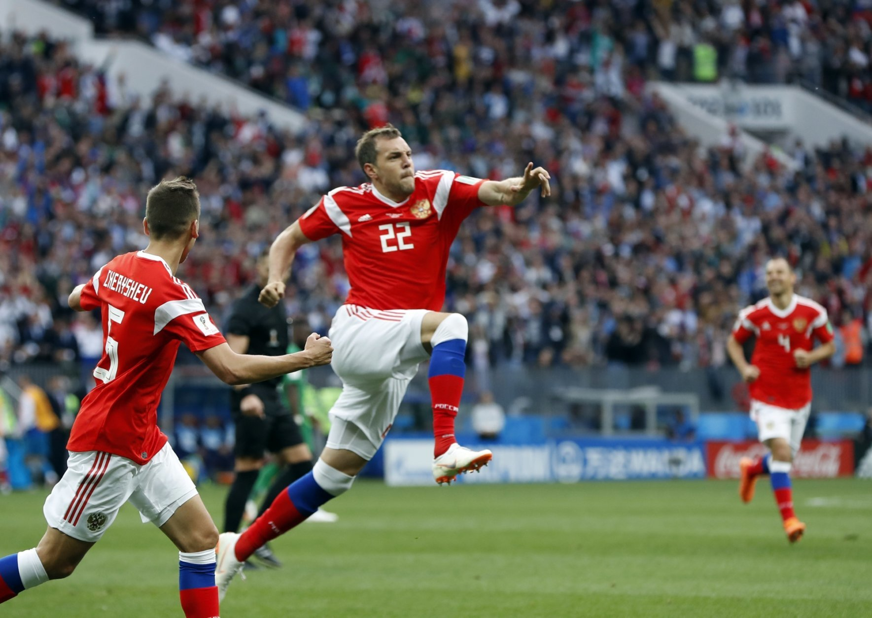 Russia's Artyom Dzyuba, center, celebrates after scoring his side's third goal during the group A match between Russia and Saudi Arabia which opens the 2018 soccer World Cup at the Luzhniki stadium in Moscow, Russia, Thursday, June 14, 2018. (AP Photo/Pavel Golovkin)