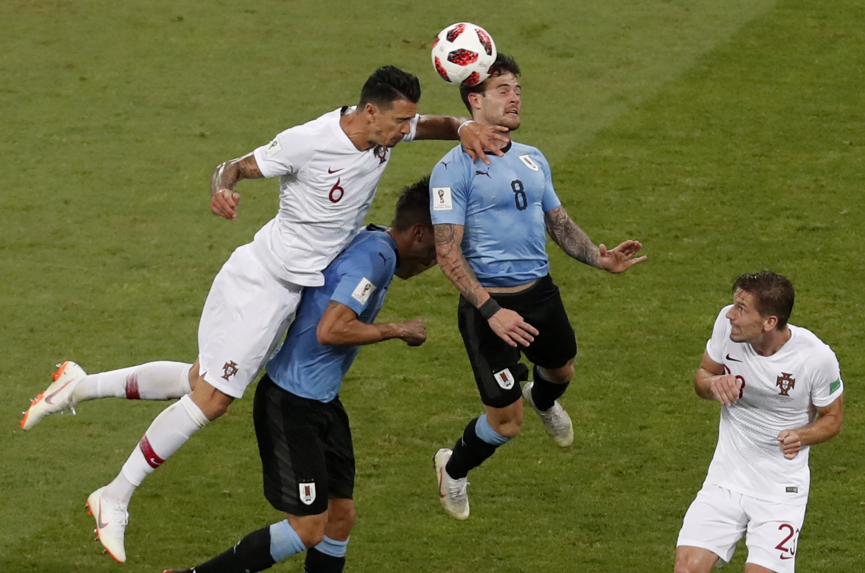 Portugal's Adrien Silva, right, look on as Portugal's Jose Fonte, left, and Uruguay's Nahitan Nandez, second right, go for a header during the round of 16 match between Uruguay and Portugal at the 2018 soccer World Cup at the Fisht Stadium in Sochi, Russia, Saturday, June 30, 2018. (AP Photo/Darko Vojinovic)