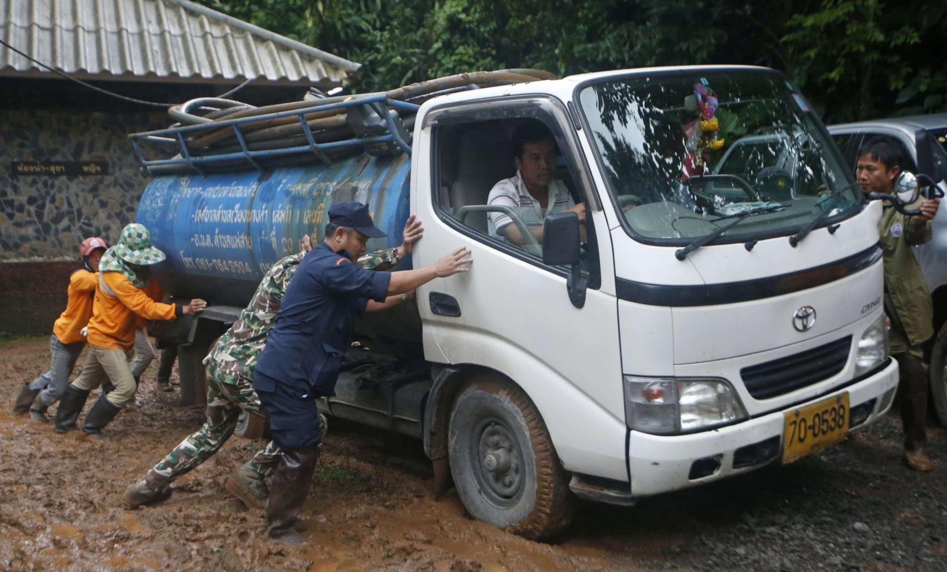 In this Thursday, June 28, 2018, photo, soldiers and volunteers push a fresh water truck stuck in mud in the staging area for the missing soccer team and their coach who are believed to be missing in a large cave in Mae Sai, Chiang Rai province, in northern Thailand. (AP Photo/Sakchai Lalit)