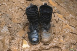 In this Thursday, June 28, 2018, photo, a pair of muddy boots sit in thick mud at the staging area for search and rescue efforts for a missing soccer team and their coach in a large cave in Mae Sai, Chiang Rai province, in northern Thailand. (AP Photo/Sakchai Lalit)