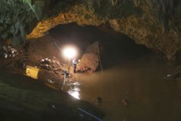 Flood water fills the entrance to a cave hindering the search efforts for 12 boys and their soccer coach who went missing in Mae Sai, Chiang Rai province in northern Thailand, Friday, June 29, 2018. (AP Photo/Sakchai Lalit)
