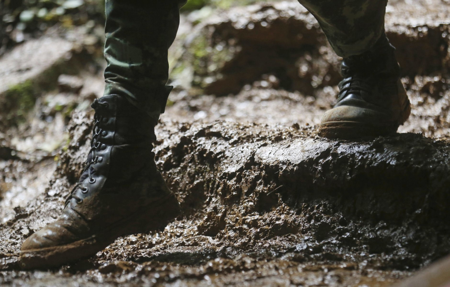 In this Thursday, June 28, 2018, photo, a soldier walks through thick mud near the cave where a soccer team and their coach went missing in a large cave in Mae Sai, Chiang Rai province, in northern Thailand. (AP Photo/Sakchai Lalit)