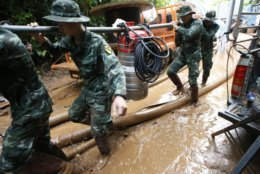 Soldiers carry a pump to help drain the rising flood water in a cave where 12 boys and their soccer coach have been missing in Mae Sai, Chiang Rai province, northern Thailand, Friday, June 29, 2018. (AP Photo/Sakchai Lalit)