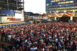 A sea of people watch the outdoor screen at The Bullpen near Nationals Park. (WTOP/Dan Friedell)