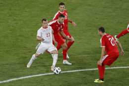 Switzerland's Xherdan Shaqiri, left, vies for the ball with Serbian defenders during the group E match between Switzerland and Serbia at the 2018 soccer World Cup in the Kaliningrad Stadium in Kaliningrad, Russia, Friday, June 22, 2018. (AP Photo/Antonio Calanni)