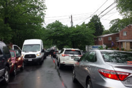 The cars on the right are parked on East Taylor Run Parkway, a two-way street that frequently gets backed up as drivers cut through the Alexandria neighborhood to get to Capital Beltway and southern Fairfax County. Drivers frequently block the street so that others coming the other way cannot use the road. This photo was taken on May 16, 2018. WTOP/Colleen Kelleher)