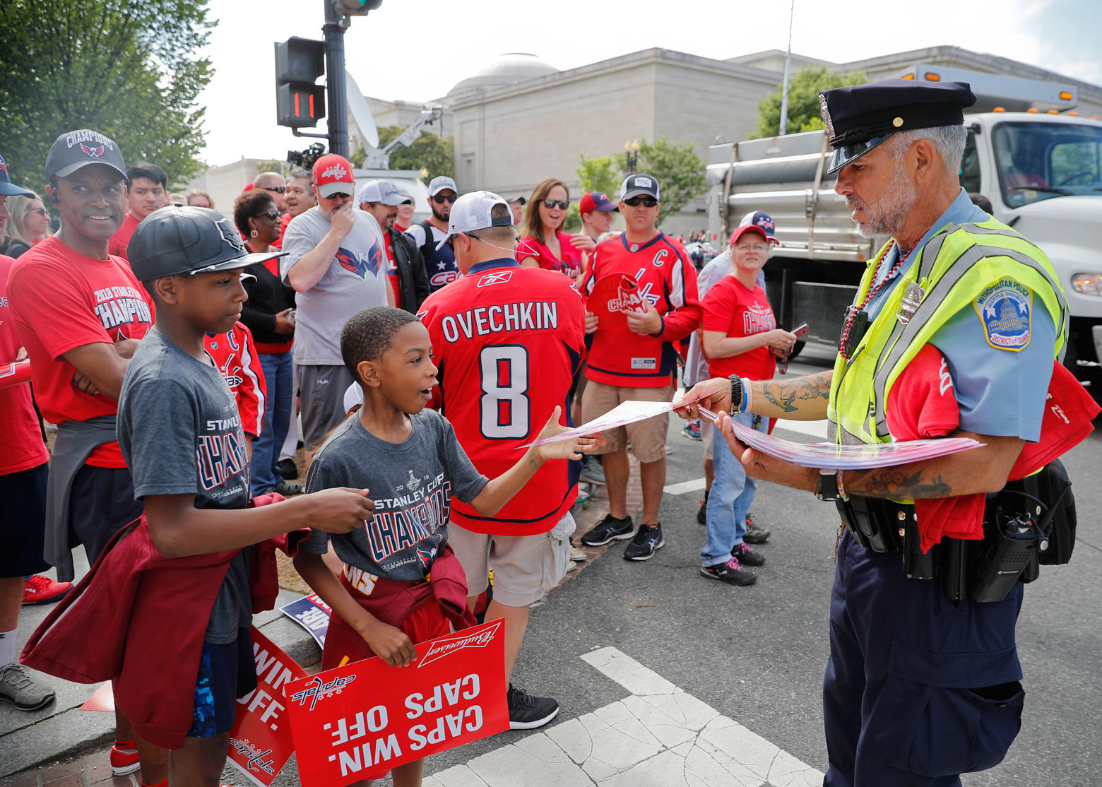Washington Metropolitan Police Officer Robert T. Fennell, right, helps hand out posters to a pair of young fans before the start the Stanley Cup victory parade on Constitution Ave., along the National Mall. (AP Photo/Pablo Martinez Monsivais)
