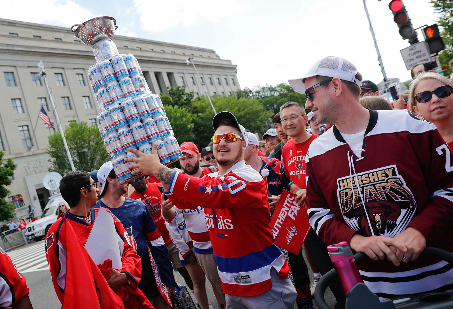 A fan carries a home-made Stanley Cup made of mostly empty beer cans as people begin to arrive for the Washington Capitals Stanley Cup victory parade on Constitution Ave., along the National Mall in Washington, Tuesday, June 12, 2018. (AP Photo/Pablo Martinez Monsivais)