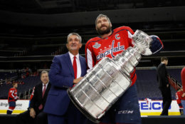 Washington Capitals NHL hockey team owner Ted Leonsis, left, and Washington Capitals left wing Alex Ovechkin, from Russia, pose for picture with the Stanley Cup on the ice at Capital One Arena, Tuesday, June 12, 2018, in Washington.