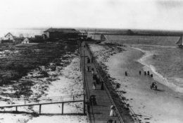 People strolling the boardwalk in Atlantic City, N.J., carry black umbrellas to ward off the sun, as horse drawn buggies wheel up and down the sandy beaches and picturesque sailboats float on the horizon, in 1895. Exact date is unknown. (AP Photo)