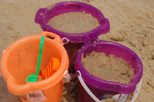 Sand is seen in buckets on the beach.