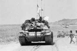 One of the last Israeli tanks to leave south Lebanon driving back into Israel on Monday, June 10, 1985 in Metulla, Israel. It was three years and four days since Israel invaded Lebanon during the Operation Peace for Oalilee. The smiling crewmen on the turret of the American-made Patton tank are holding a sigh; saying in Hebrew 'Stop', Border is in front of you. (AP Photo/Max Nash)