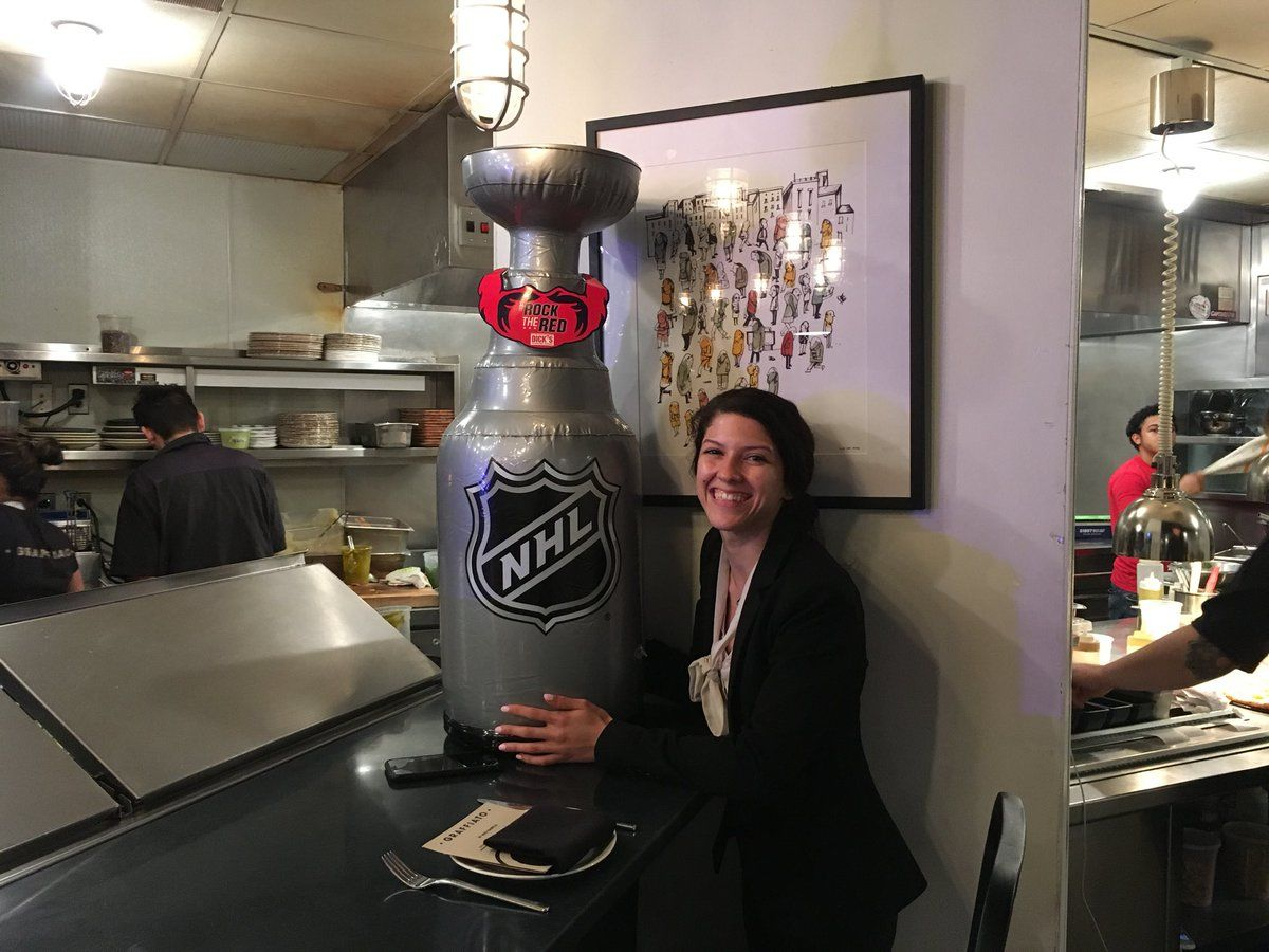 Fernanda Bernardes, of Graffiato DC, with a blow-up replica of the Stanley Cup ... and an Ovechkin beard. (WTOP/Liz Anderson)