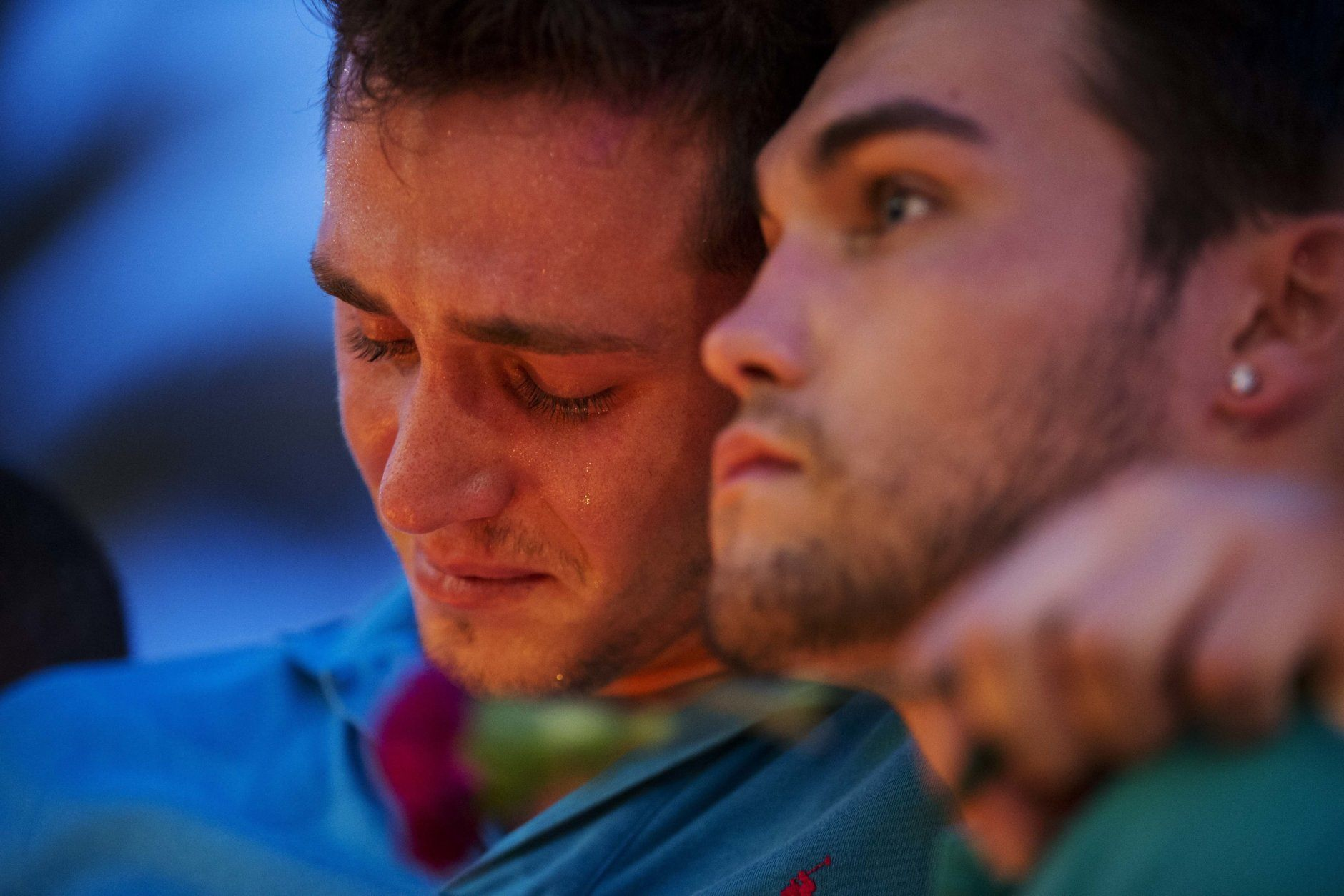Austin Hagge, left, cries on the shoulder of Austin Matthew, during a candlelight vigil downtown for the victims of a mass shooting at the Pulse nightclub Monday, June 13, 2016, in Orlando, Fla. Hagge and Matthew lost two friends in the shooting. A gunman has killed dozens of people in a massacre at a crowded gay nightclub in Orlando on Sunday, making it the deadliest mass shooting in modern U.S. history. (AP Photo/David Goldman)