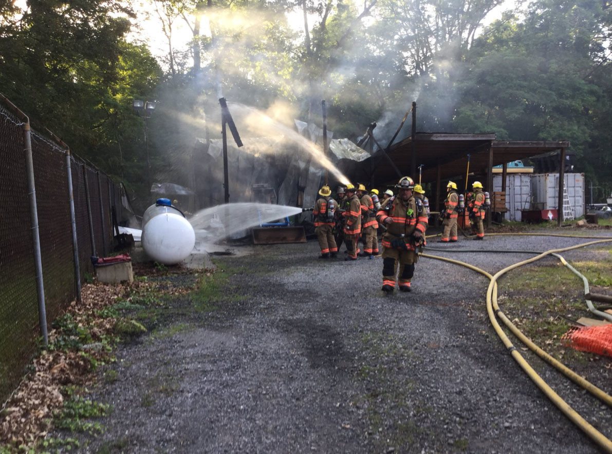 Firefighters also cool down a nearby fuel tank hose that was releasing gas out of the valve during a fire at Seneca Creek State Park on Saturday, June 16, 2018. (Courtesy Montgomery County Fire and EMS)