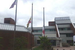 The state flag of Maryland and the flag of Howard County fly at half mast in honor of National Guardsman Eddison Hermon who was killed when floodwaters rushed through Ellicott City on May 27, 2018. (WTOP/Kathy Stewart)