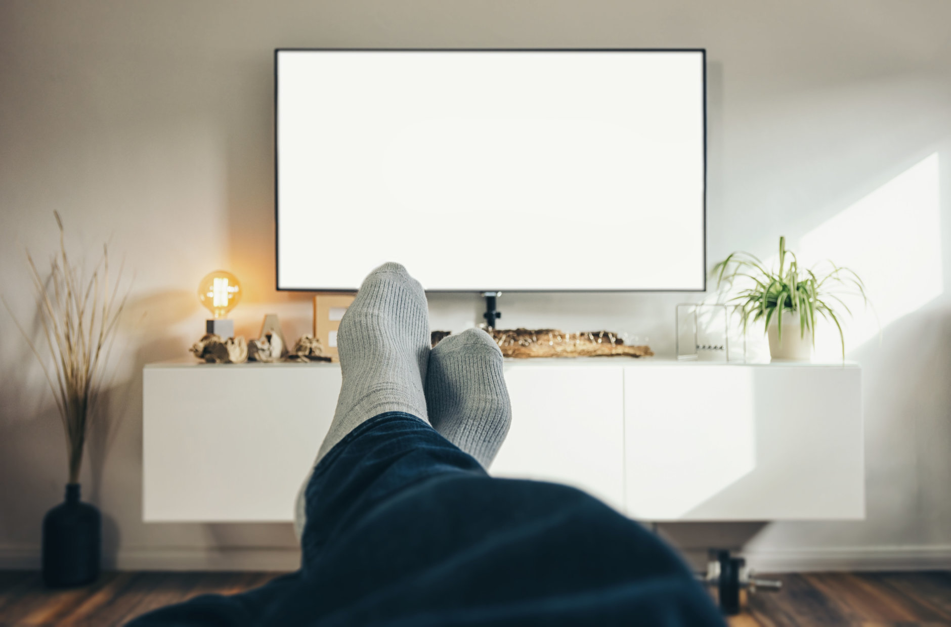 POV-Shot from a young watching tv with his feets and socks at home, including copy space. ideal for websites and magazines layouts