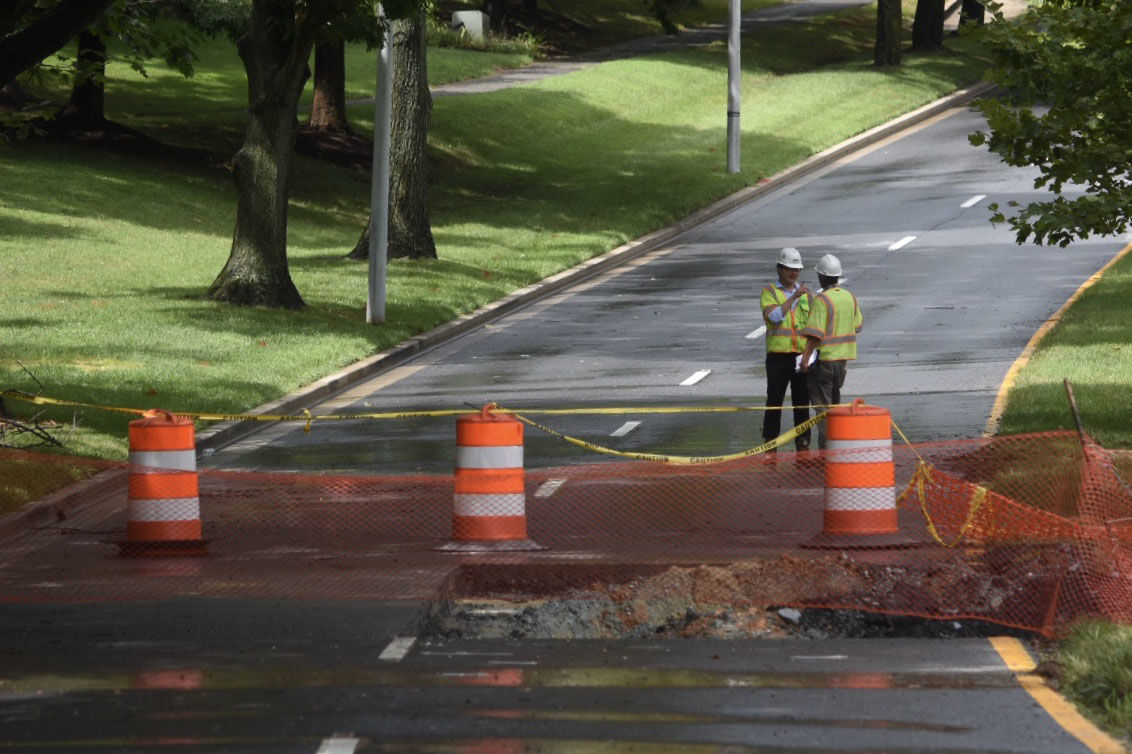 The work to fix the flood-damaged section of Father Hurley Boulevard between Crystal Rock Drive and Middlebrook Road in Germantown, Maryland, continued July 24  despite occasional downpours. (WTOP/Dave Dildine)