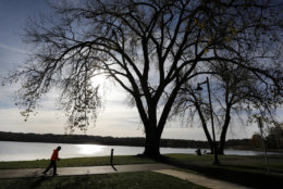 A man walks on the path around Gray's Lake Park, Tuesday, Oct. 31, 2017, in Des Moines, Iowa. (AP Photo/Charlie Neibergall)