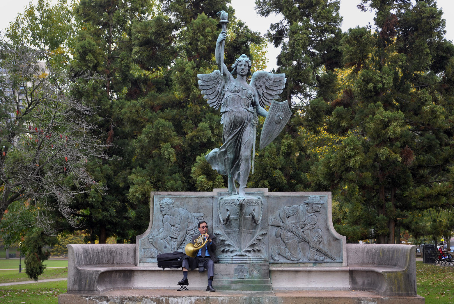 Victor Perpetua plays his French horn seated under a statue of the Spirit of Victory in Bushnell Park in Hartford, Conn., Tuesday, Oct. 23, 2012.  Perpetua is an attorney in the city and often comes out to the park to play his horn on his lunch break.  (AP Photo/Jessica Hill)