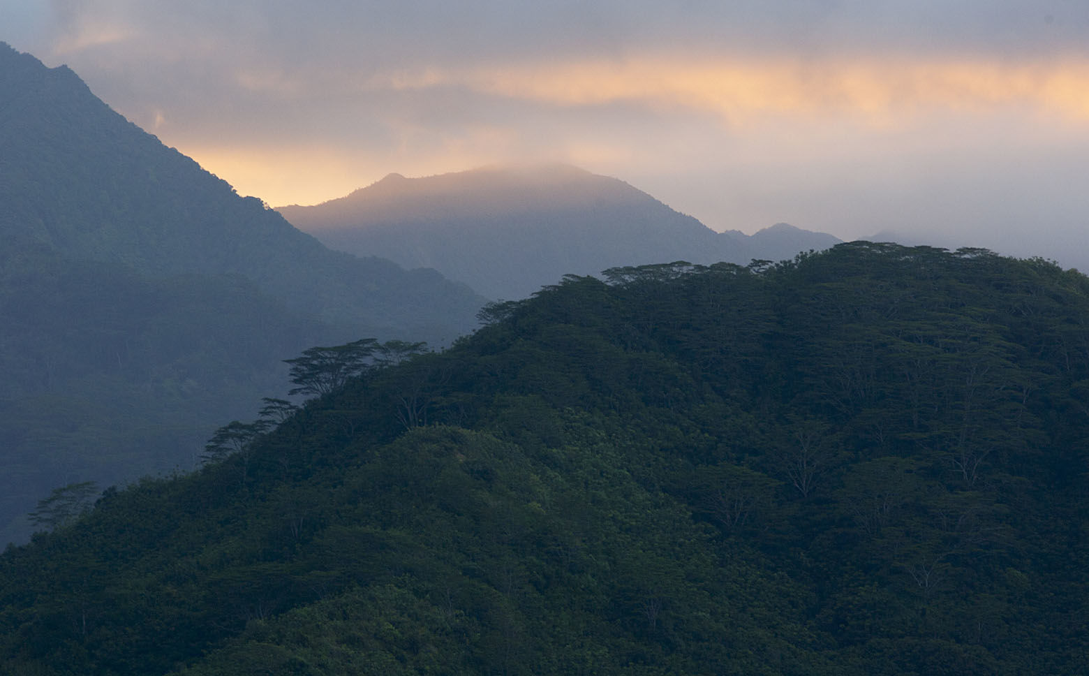 The sun sets behind mountains near Kaneohe, Hawaii, Monday, May 4, 2015. (AP Photo/Caleb Jones)