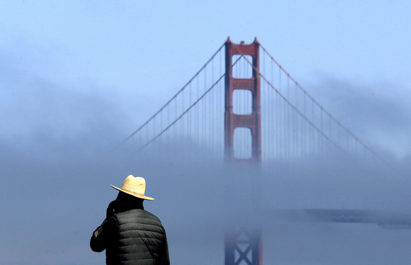 A man stands at China Beach as fog rolls past a span of the Golden Gate Bridge in San Francisco, Thursday, Sept. 28, 2017. (AP Photo/Jeff Chiu)