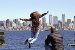 Mariel Toledo leaps for a photo taken by her friend Chi Nguyen in view of downtown Seattle on an unusually sunny day Friday, April 21, 2017. Rain is expected to return Saturday and continue for at least several days. (AP Photo/Elaine Thompson)