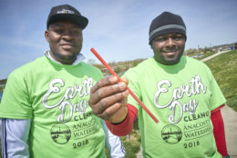 Volunteers at Bladensburg Waterfront Park hold up a straw they collected during the Anacostia Watershed Society Earth Day Cleanup. (Courtesy Dwayne Grimes/Anacostia Watershed Society)