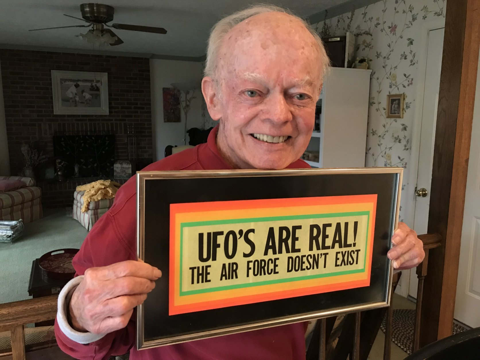 Shea holds a funny sign that used to hang in his office. It was given to him by journalist and UFO skeptic Phil Klass. (WTOP/Michelle Basch)