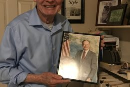 Shea holds a photo of himself taken during his time in the Air Force. (WTOP/Ginger Whitaker)