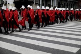 Pro-choice activists in favor of decriminalizing abortion wear costumes from the Handmaid's Tale, a book and now television series, outside Congress where lawmakers passed new, abortion-related legislation which is scheduled to be voted on by the Senate, in Buenos Aires, Argentina, Wednesday, July 25, 2018. The novel's writer, Margaret Atwood, showed her support on Twitter for approval of the law, which would legalize elective abortion in the first 14 weeks of pregnancy. (AP Photo/Natacha Pisarenko)
