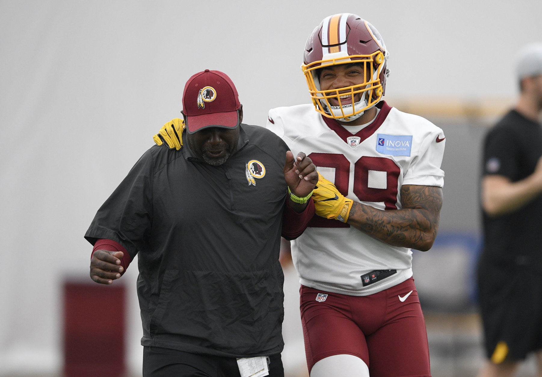 Washington Redskins running back Derrius Guice (29) jokes around with a coach during an NFL football team practice, Wednesday, June 13, 2018, in Ashburn, Va. (AP Photo/Nick Wass)