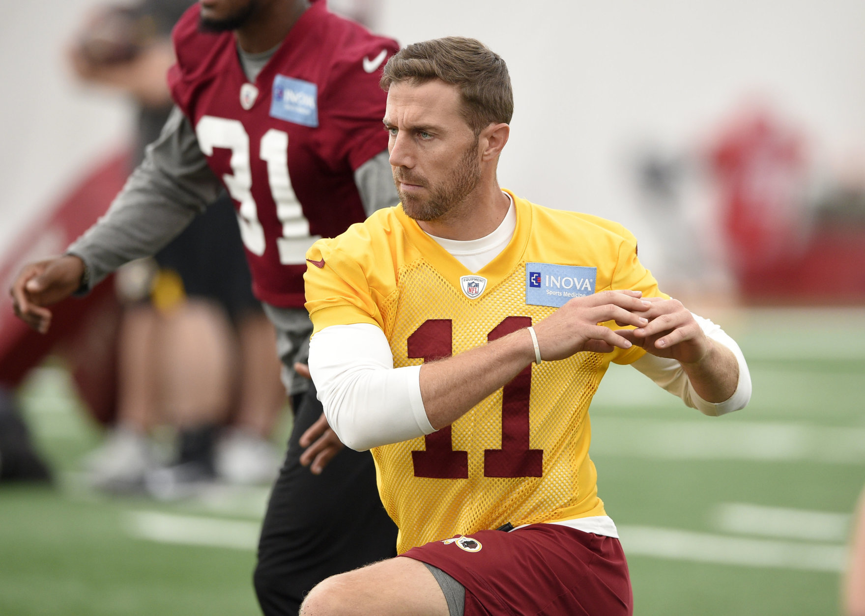 Washington Redskins quarterback Alex Smith (11) stretches during an NFL football team practice, Wednesday, June 13, 2018, in Ashburn, Va. (AP Photo/Nick Wass)