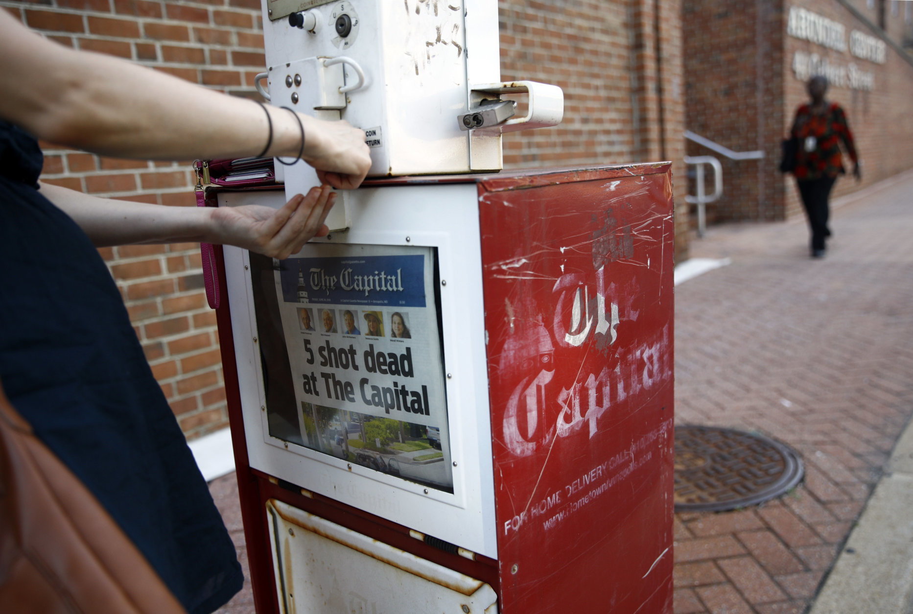 Angela Gentile, of College Park, Md., tries to buy a copy of The Capital Gazette from a newspaper rack, Friday, June 29, 2018, in Annapolis, Md. A man armed with smoke grenades and a shotgun attacked journalists in the newspaper's building Thursday, killing several people before police quickly stormed the building and arrested him, police and witnesses said. (AP Photo/Patrick Semansky)