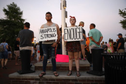 Tanner Piekarski, left, and Kylie Myles hold signs during a vigil in response to a shooting at The Capital Gazette newspaper office, Friday, June 29, 2018, in Annapolis, Md. Prosecutors say Jarrod W. Ramos opened fire Thursday in the Capital Gazette newsroom. (AP Photo/Patrick Semansky)